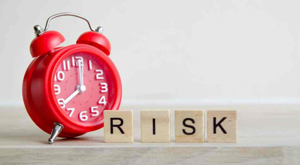 Red Alarm Clock with block letter that say RISK.