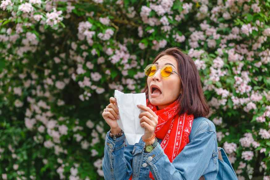 Young Asian women sneezing due to the trees in bloom.