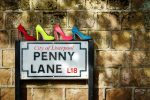 four pairs of ladies shoes, in colours of Sergeant Pepper, atop of the Penny Lane street sign in Liverpool