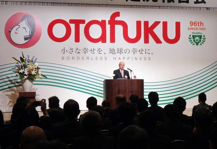 新ロゴの前で方針を語る佐々木直義社長(オタフクソース)