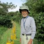 徳之島コーヒー生産者会の吉玉誠一代表(吉玉農園)と新植した苗木