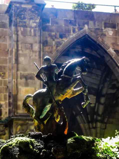 A statue in the dappled sunlight of Barcelona Cathedral cloisters