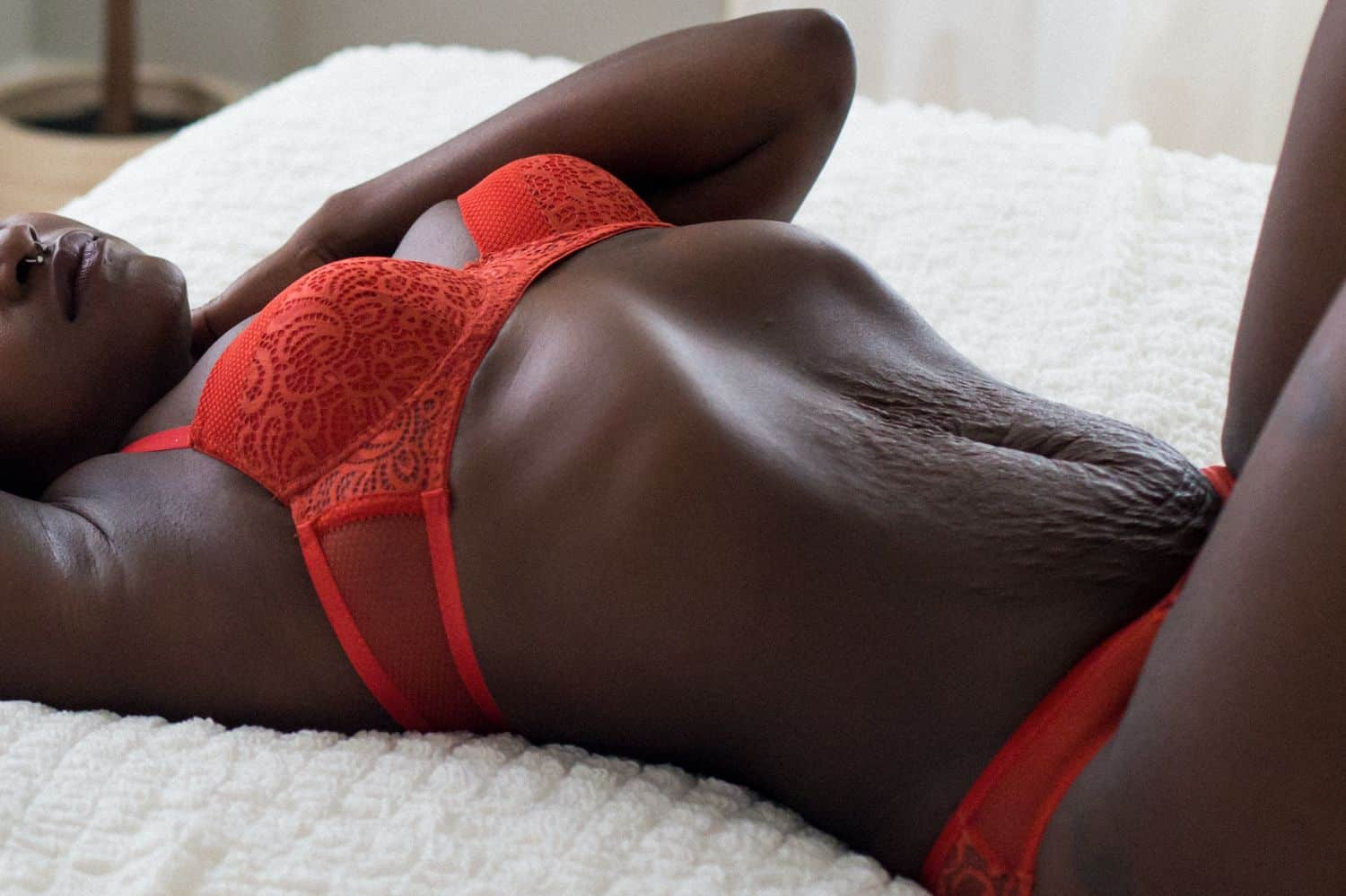 A dark-skinned person in deep orange lingerie reclines back on a white bed. The Empowerment Photographer is highlighting this individuals beautiful curves, lines, and angles.
