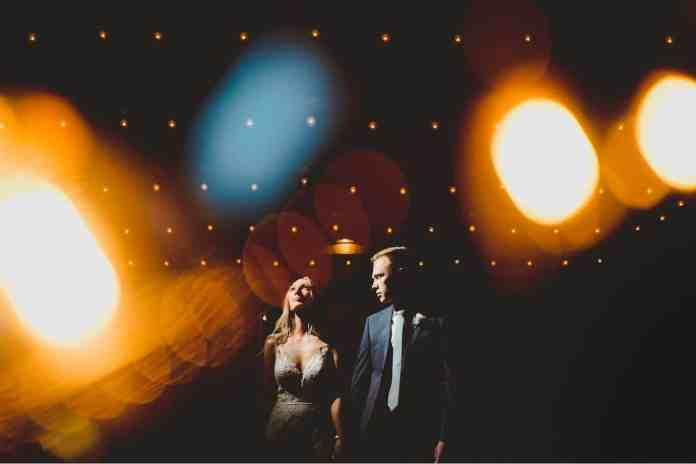 Black & Gold Photography created this double-exposure wedding portrait using off-camera flash. The bride stands at the center of the frame looking toward the bright light. The groom looks toward the light with his face angled toward the bride. They are surrounded by dream-like globes of light that were made using the double exposure technique.
