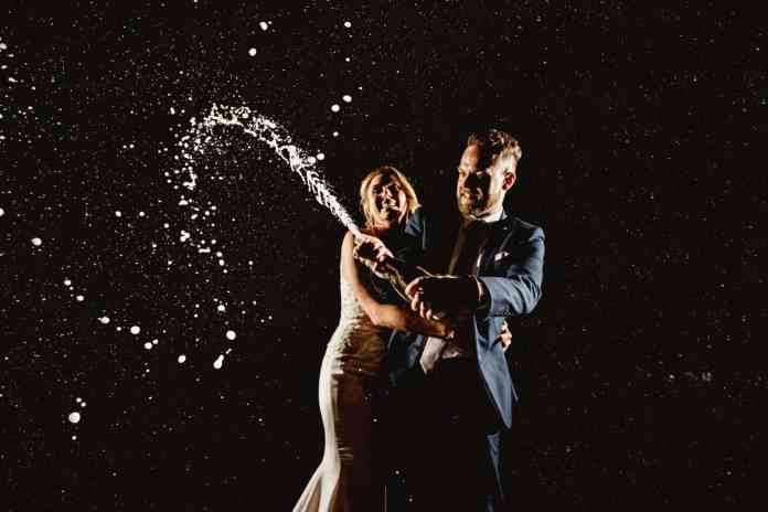 A wedding couple stands against a nighttime backdrop and pops a fresh bottle of champagne. The bride's face is jubilant and her arms encircle the groom as he pops the bottle's cork with determination on his face. Black & Gold Photography makes amazing wedding portraits using off-camera flash.