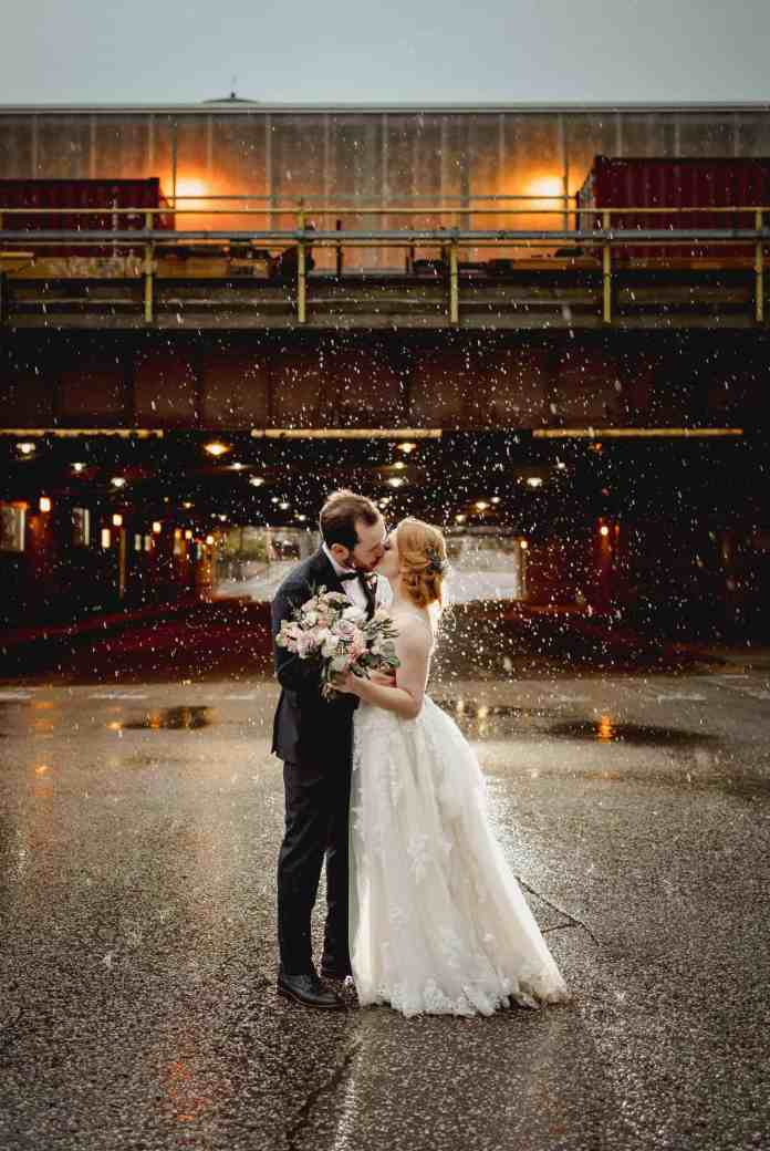 A bride and groom stand kissing in the middle of the road. A train trestle looms behind them, and rain pours all around them. Black & Gold Photography uses this photograph to teach photographers how to make wedding portraits using off-camera flash.