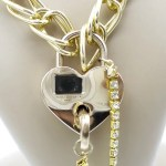 Close up of gold heart shaped padlock with key attached by gold rhinestone chain.