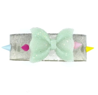 Front view of glitter infused resin cuff with rainbow spikes and mint green bow in center