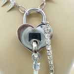 Closeup of silver heart shaped padlock with spiked rhinestone chain. Key attached with silver rhinestone chain.