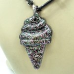 Closeup of black resin soft serve ice cream pendant infused with glitter