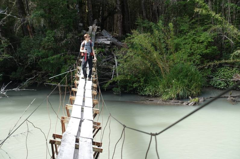 Kyle on suspension bridge above Rio Frías's milky green waters