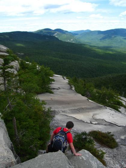 A hiker descends the ledges on South Baldface