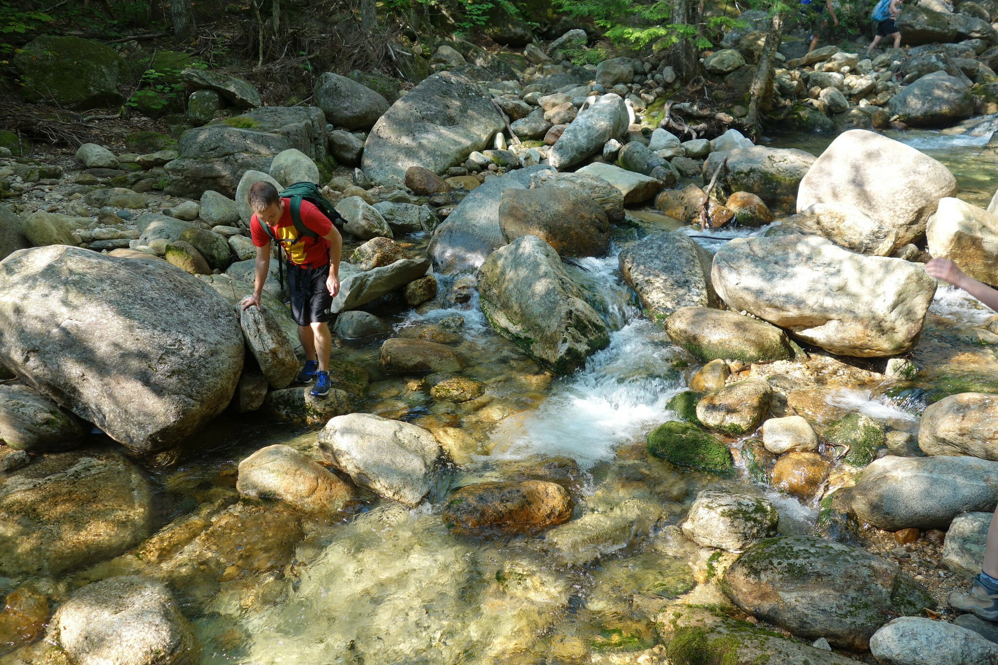 Hiker crosses a stream on the Baldface Circle Trail, White Mountains, New Hampshire