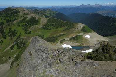 View of a green ridge, blue tarn, and several jagged North Cascades Peaks from Skyline Divide