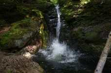 A large splash from a hiker jumping into Kees Falls