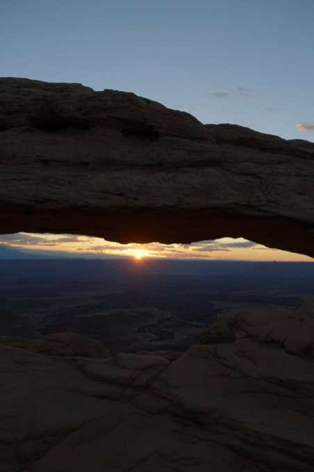The sun begins to appear on the horizon, seen through Mesa Arch, Canyonlands National Park