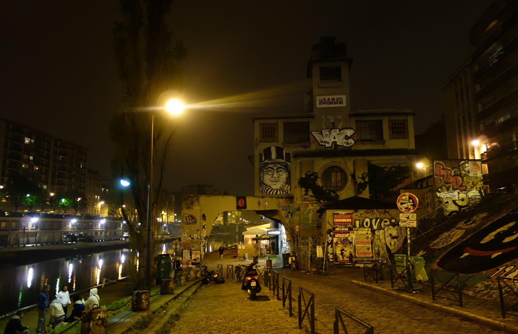 Point Éphémère, a music venue and café along the Canal St-Martin, at night.