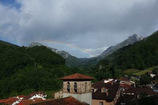 A rainbow appears above mountains and the town of Espinama