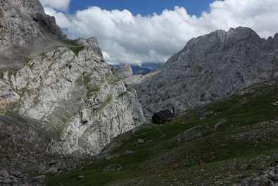 Refugio Collado Jermoso, steep limestone cliffs, and mountains