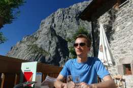 Kyle sits on a patio, with a stone building and mountain in the background