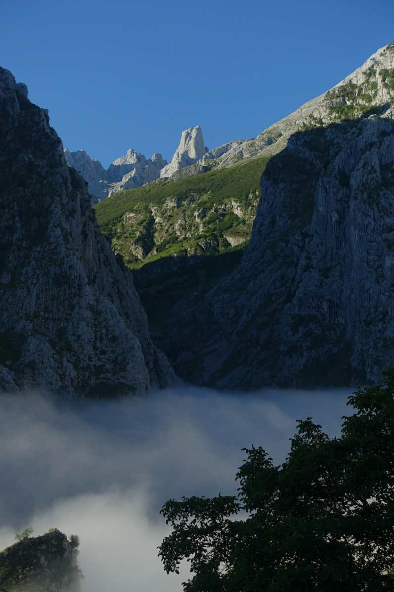 Morning light illuminates Naranjo de Bulnes while mists lift in the valley below