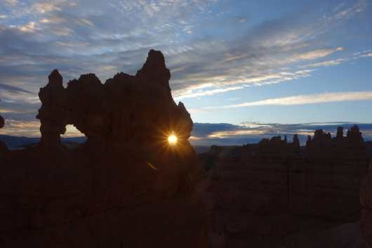 The sun rises through a small window in a hoodoo