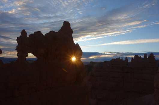 The sun rises through a small window in a hoodoo