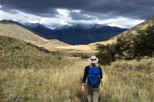 Sean and the Avilés Loop trail in the foreground, continuing onward across a wide, grassy plateau with snowcapped mountains and stormy clouds in the background