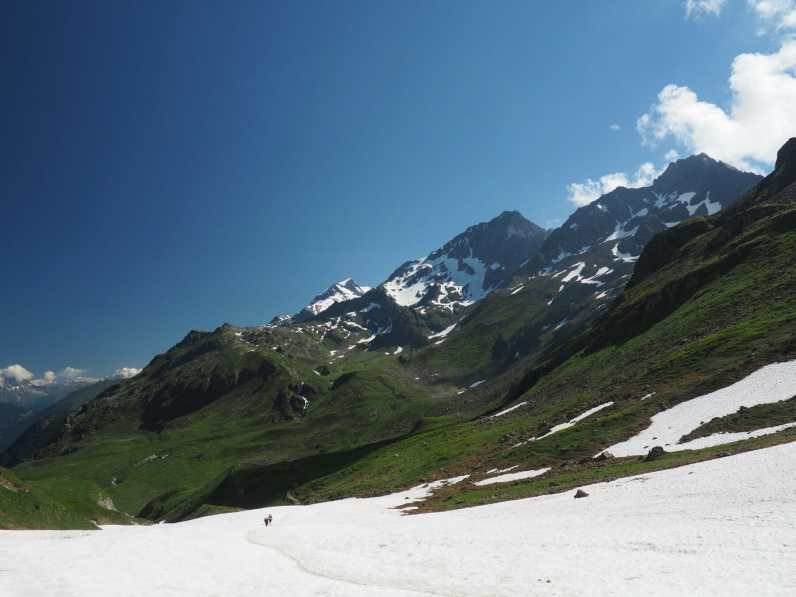 hikers descend a long snowfield below Col du Bonhomme