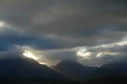 Golden light cuts through the grey clouds