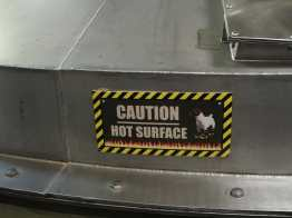 "Sign that reads: ""Caution, hot surface"" with a dog warning fire boots."