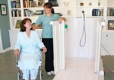 picture shows a woman in wheelchair in front of shower bay - a portable shower meant for wheelchair users
