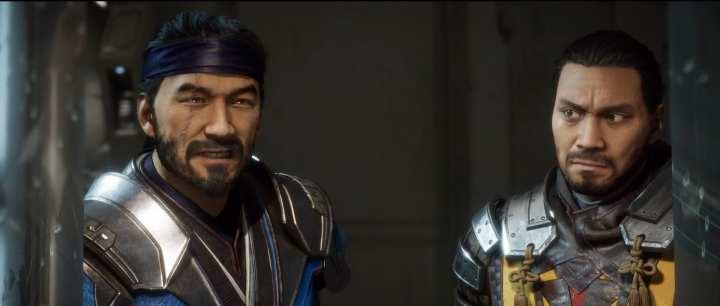 Os ninjas Sub Zero e Scorpion, lado a lado sem máscaras. Scorpion olha com expressão de dúvida para Sub Zero.