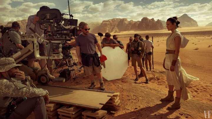 Foto mostra a personagem Rey no deserto junto a equipe de gravação de Star Wars e o diretor J.J Abrams
