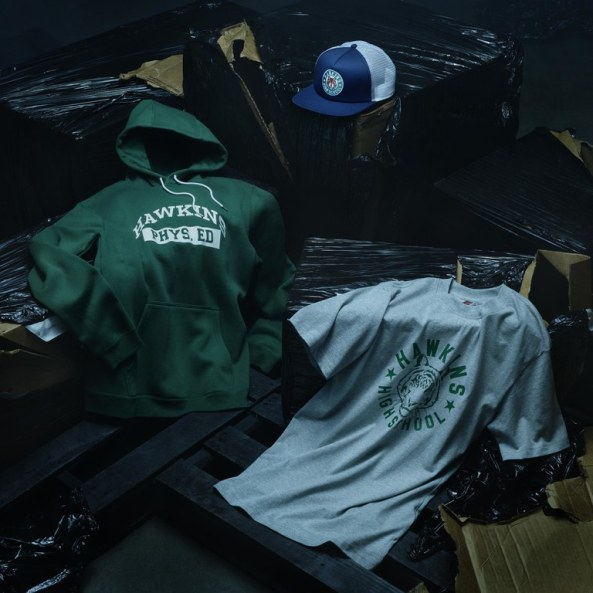 O vestuário inclui camisas, bonés e agasalhos com o logo do colégio Hawkins.