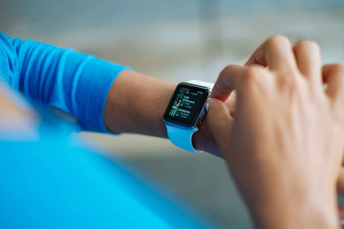 person in blue long sleeve shirt using smart watch