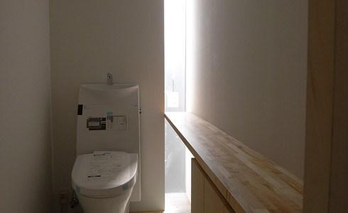 壁のスリットから光が差すトイレ