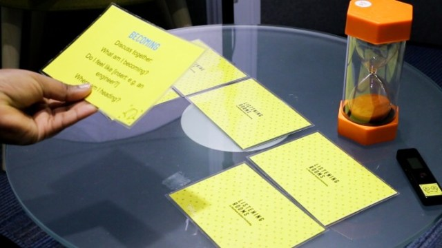 Discussion prompt cards on a table with a sand timer which was used in the Listening Rooms project.
