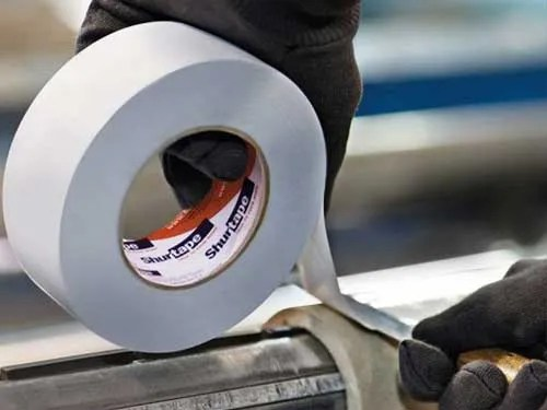 Industrial tape being applied to a steel pipe