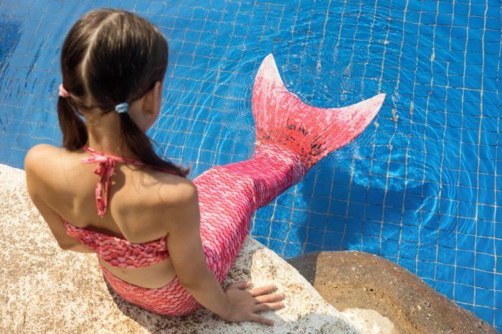 Chica sirena con cola rosa en la roca junto a la piscina puso los pies en el agua.