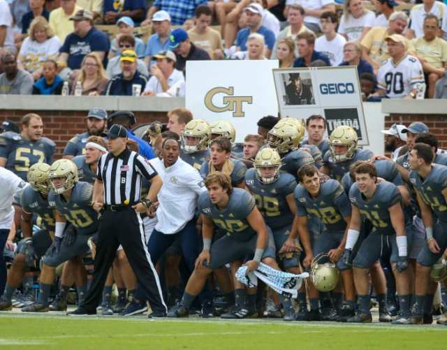Georgia Tech football holds up signs for play calls on the sideline