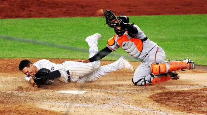 Baltimore Orioles catcher Pedro Severino (28) tags out New York Yankees third baseman Gio Urshela (29) at home plate to end the game on a double play in the 11th inning at Yankee Stadium.
