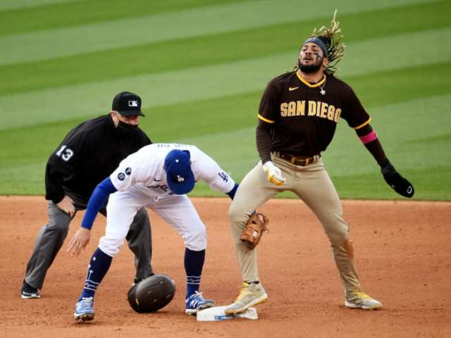 Apr 25, 2021; Los Angeles, California, USA; San Diego Padres shortstop Fernando Tatis Jr. (23) tosses his hair after stealing second base against Los Angeles Dodgers second baseman Chris Taylor (3)during the sixth inning at Dodger Stadium.