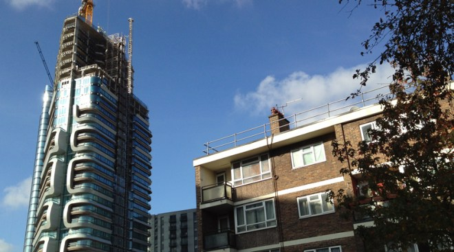 Modern tower block under construction next to traditional council housing