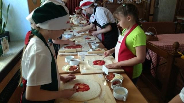 Children are spreading tomato sauce on pizza dough at Mama Roma's.