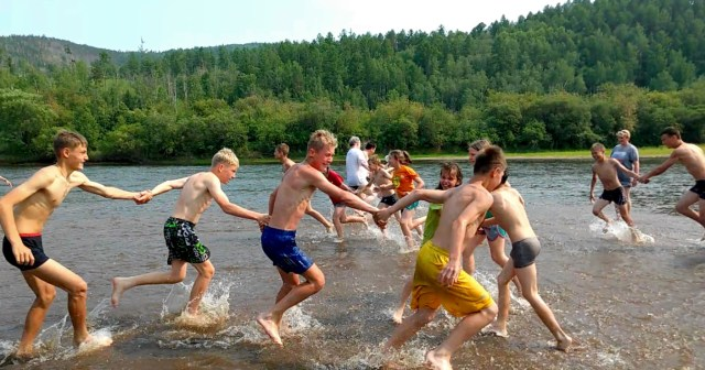 children running and holding hands on a sand bar in a river