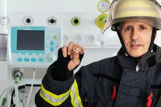 Der kleinste Feuerlöscher der Welt in den Händen eines Feuerwehrmannes vor einem Beatmungsgerät.