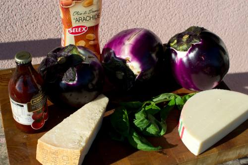 Ingredients glamour shot. 3 Eggplants. Parmigiana on the left and caciocavallo on the right. Peanut oil in back. These are not the correct portions for each item.