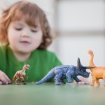 Child with autism playing with dinosaurs.