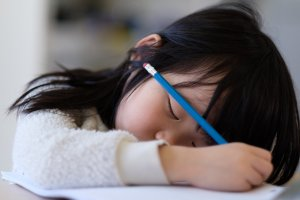 Child with autism spectrum disorder sleeping at her desk, with pencil in hand.